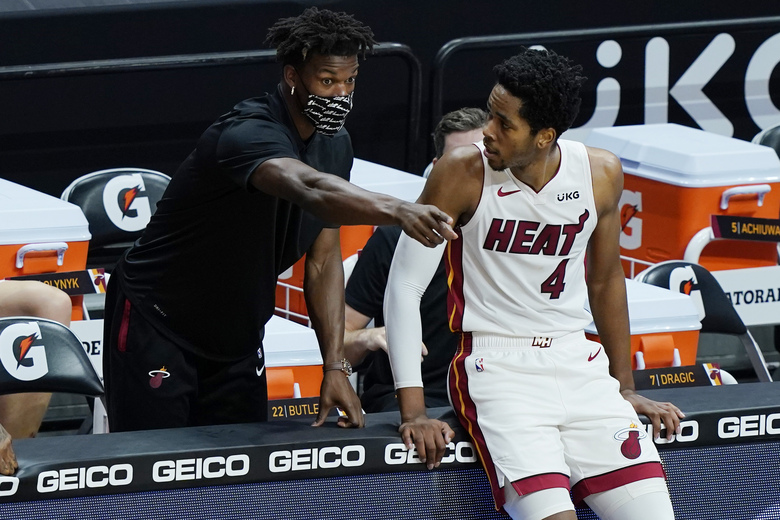 Miami Heat forward KZ Okpala (4) listens to teammate Jimmy Butler during the first half of an NBA basketball game against the Denver Nuggets, Wednesday, Jan. 27, 2021, in Miami. Butler has missed multiple games because of the NBA's health and safety protocols. (AP Photo/Marta Lavandier)