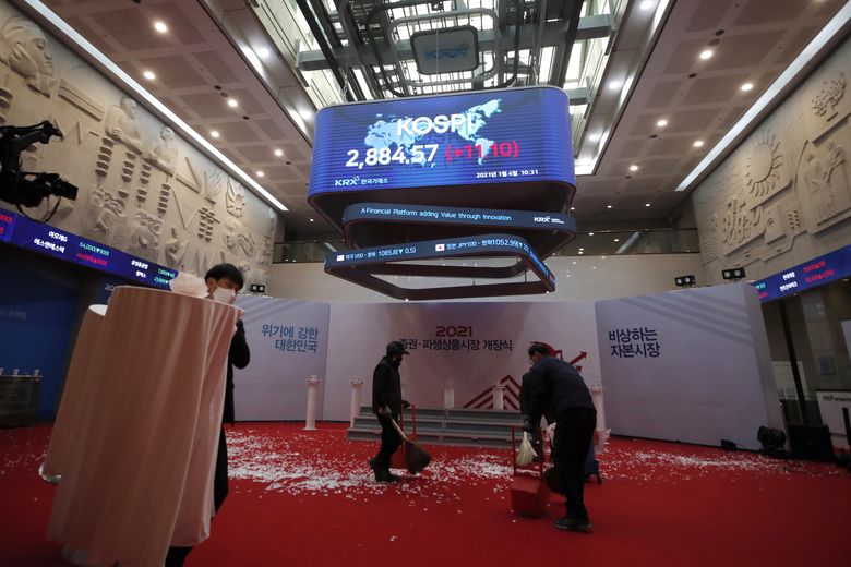 A huge screen shows the Korea Composite Stock Price Index (KOSPI) as workers clear the floor after the opening ceremony of the 2021 trading year at the Korea Exchange in Seoul, South Korea, Monday, Jan. 4, 2021. Asian stock markets rose on 2021's first trading day, boosted by optimism about the rollout of coronavirus vaccines after Wall Street ended the year on a new high. (AP Photo/Lee Jin-man)