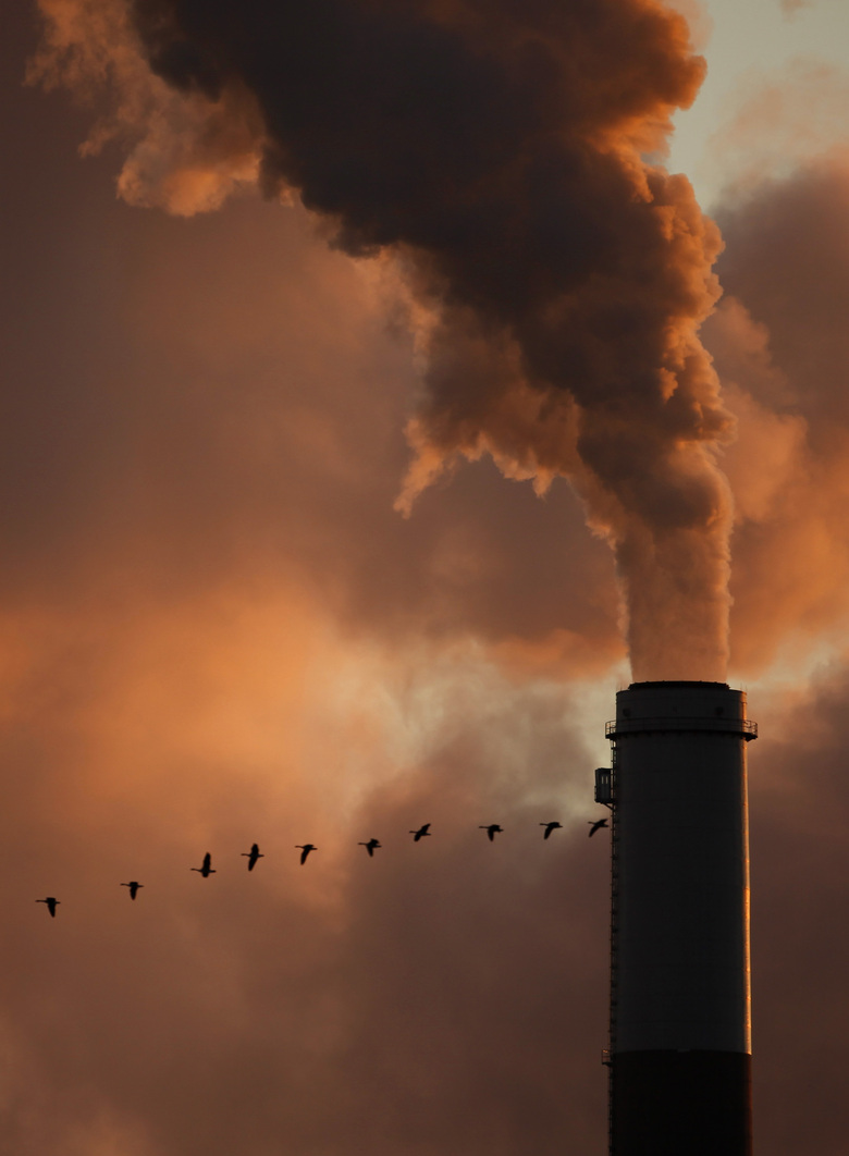 FILE – The Jan. 10, 2009 file photo shows a flock of geese flying past a smokestack at the Jeffery Energy Center coal power plant near Emmitt, Kan. A new study says the amount of global warming already baked into the air because of past carbon pollution is enough to blow past internationally agreed upon climate limits. A study on Monday, Jan. 4, 2021 takes a different look at what's called committed warming that comes from heat-trapping gases staying in the atmosphere for more than a century. (AP Photo/Charlie Riedel, File)