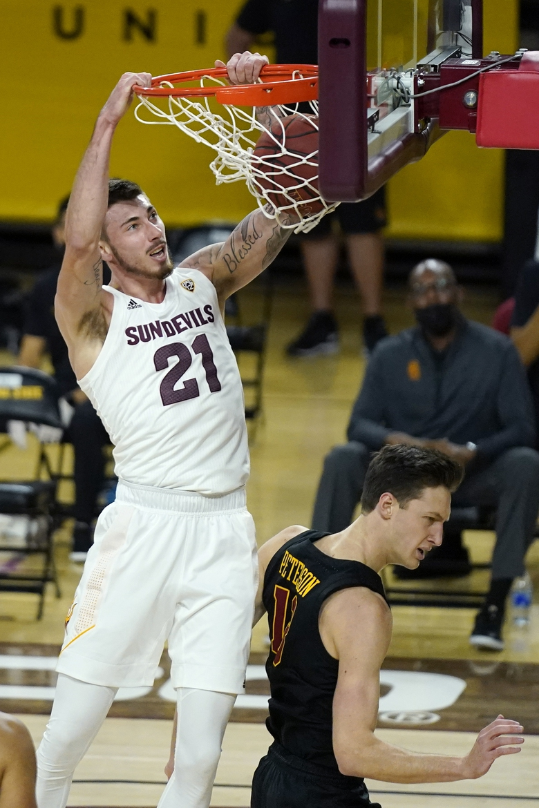 Arizona State forward Chris Osten, left, dunks on USC guard Drew Peterson, right, during the first half of an NCAA men's college basketball game Saturday, Jan. 9, 2021, in Tempe, Ariz. (AP Photo/Ross D. Franklin)