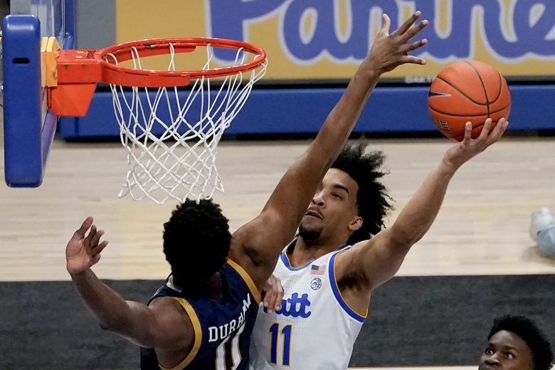 Pittsburgh's Justin Champagnie, center right, shoots as Notre Dame's Juwan Durham, left, defends during the first half of an NCAA college basketball game, Saturday, Jan. 30, 2021, in Pittsburgh. (AP Photo/Keith Srakocic)