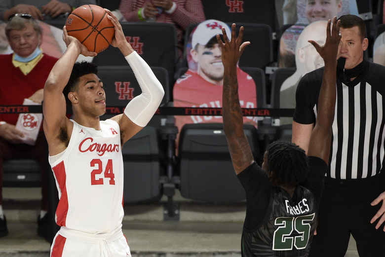 Houston guard Quentin Grimes (24) looks to pass as Tulane guard Jaylen Forbes (25) defends during the first half of an NCAA college basketball game, Saturday, Jan. 9, 2021, in Houston. (AP Photo/Eric Christian Smith)