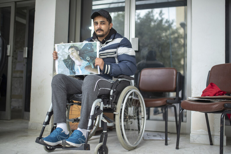 Rached El Arbi, 30, a protester who was paralyzed after being shot during Tunisia's democratic uprising 10 years ago, poses for a portrait while holding an image of himself, in Tunis, Tunisia, Tuesday, Jan. 12, 2021. El Arbi, now 30, has been paralyzed since being shot while protesting the autocratic regime of Tunisia's President Zine El Abidine Ben Ali, who was overthrown on Jan. 14, 2011. A photo of El Arbi hospitalized at the time went viral across the Arab world. (AP Photo/Mosa'ab Elshamy)