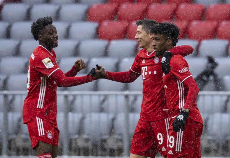 Alphonso Davies, Robert Lewandowski and Kingsley Coman of Munich, from left, celebrate the opening goal during the Bundesliga soccer match between Bayern Munich and SC Freiburg in Munich, Germany, Sunday, Jan. 17, 2021. Photo: (Sven Hoppe/dpa via AP)