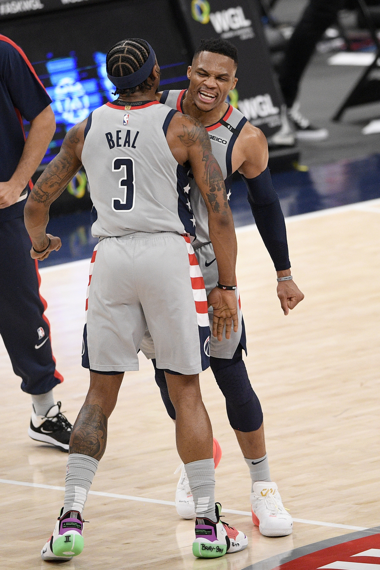 Washington Wizards guard Russell Westbrook, back, reacts with guard Bradley Beal (3) after he made a three-point basket during the second half of an NBA basketball game against the Brooklyn Nets, Sunday, Jan. 31, 2021, in Washington. (AP Photo/Nick Wass)