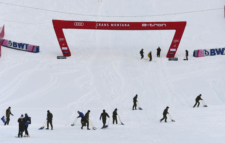 Course crew work at the finish area after an alpine ski, women's World Cup downhill postponed due to heavy snowfall, in Crans Montana, Switzerland, Friday, Jan. 22, 2021. (AP Photo/Marco Tacca)