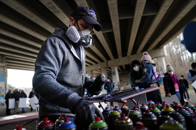 Artist Brandon Litman looks for a color to paint a U.S. Senator-elect Jon Ossoff, D-Ga., campaign poster for voters waiting in line after Georgia's Senate runoff race on Jan. 10 in Atlanta. (AP Photo/Brynn Anderson)