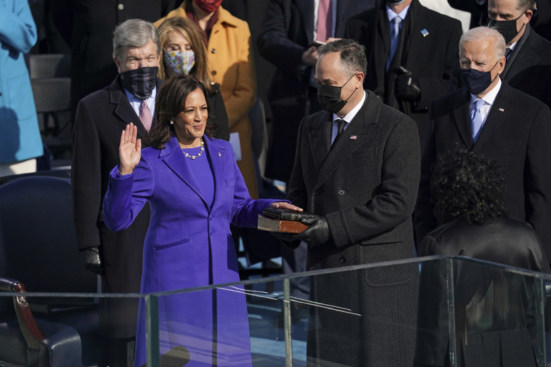 FILE – Kamala Harris is sworn in as vice president by Supreme Court Justice Sonia Sotomayor as her husband Doug Emhoff holds the Bible during the 59th Presidential Inauguration at the U.S. Capitol in Washington, Wednesday, Jan. 20, 2021.   On Friday, Jan. 22, The Associated Press reported on stories circulating online incorrectly claiming Kamala Harris put her hand on a purse instead of a Bible during her swearing in.  (Erin Schaff/The New York Times via AP, Pool, File)