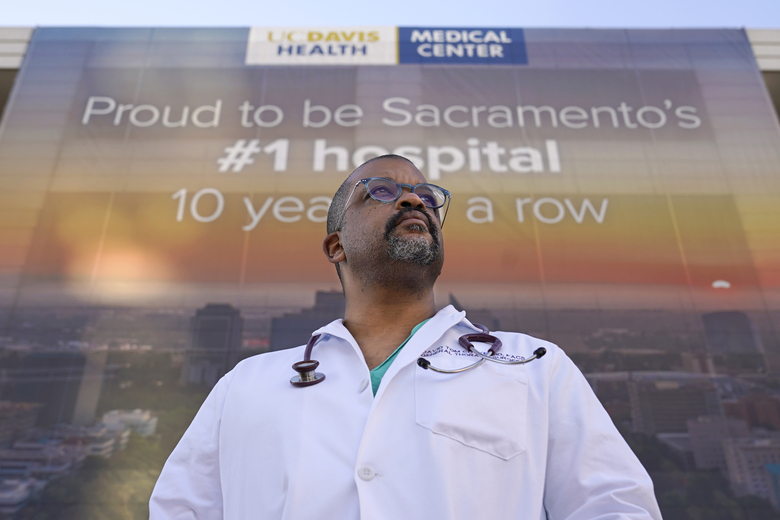 Dr. David Tom Cooke, head of general thoracic surgery at UC Davis Health, poses outside the UC Davis Medical center in Sacramento, Calif., Friday, Dec. 18, 2020. Cooke participated in Pfizer's clinical trial for the coronavirus as part of an effort to reduce skepticism about the vaccine among the Black community. He's now promoting the vaccine's safety and the importance of taking it on his social media pages. (AP Photo/Rich Pedroncelli)