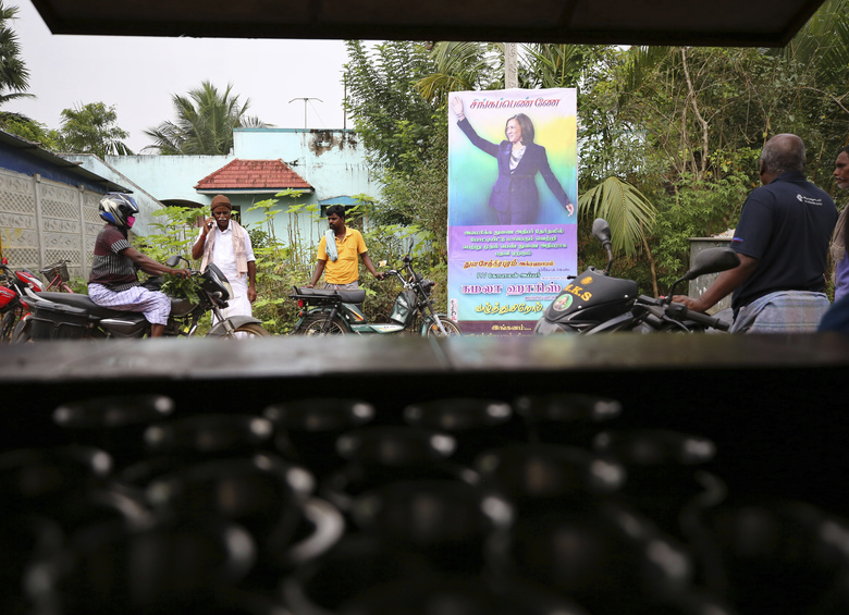 Indian villagers gather outside a local eatery next to a banner featuring U.S. Vice President-elect Kamala Harris with a message wishing her best, in Thulasendrapuram, the hometown of Harris' maternal grandfather, south of Chennai, Tamil Nadu state, India, Wednesday, Jan. 20, 2021. A tiny village in a remote part of South India is gearing up for celebrations ahead of Kamala Harris' inauguration as the first female vice president of the United States. (AP Photo/Aijaz Rahi)