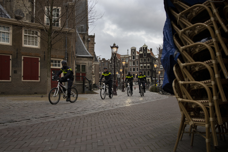 FILE – In this Jan. 14, 2021, file photo, police officers on bicycles pass stacked up terrace chairs outside a bar in the near-empty Red Light District in Amsterdam. The Dutch government this week extended by three weeks the tough lockdown in force since mid-December amid fears that coronavirus infection rates are not declining quickly enough and fears about a new more transmissible variant of the COVID-19 virus. (AP Photo/Peter Dejong)