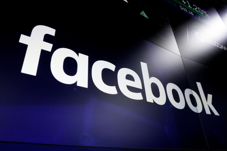 FILE – This March 29, 2018 file photo shows the Facebook logo on screens at the Nasdaq MarketSite, in New York's Times Square. The U.K.'s competition watchdog launched a formal investigation on Thursday Jan. 28, 2021 into Facebook's purchase of Giphy over concerns it will stifle competition for animated images. (AP Photo/Richard Drew, File)