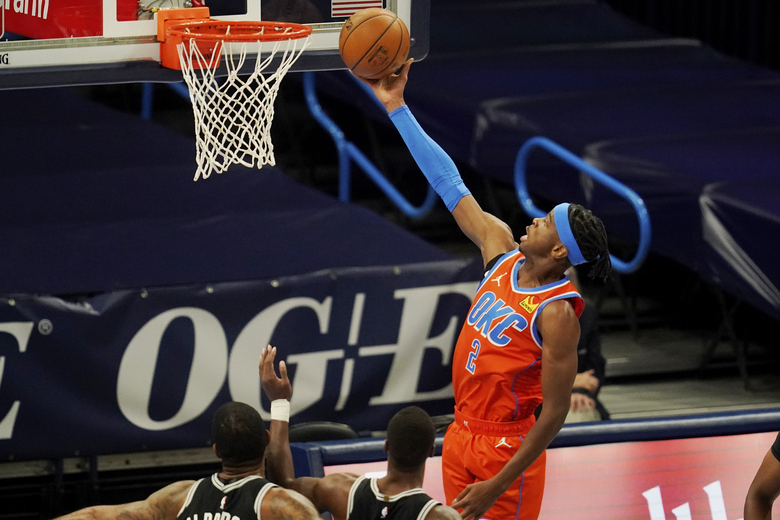 Oklahoma City Thunder guard Shai Gilgeous-Alexander (2) shoots in front of San Antonio Spurs center LaMarcus Aldridge, left, and guard Lonnie Walker IV during the first half of an NBA basketball game Tuesday, Jan. 12, 2021, in Oklahoma City. (AP Photo/Sue Ogrocki)