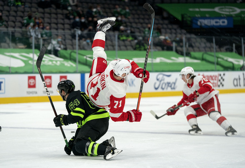 Detroit Red Wings center Dylan Larkin (71) is upended by Dallas Stars center Tanner Kero (64) during the first period of an NHL hockey game Thursday, Jan. 28, 2021, in Dallas. (AP Photo/Jeffrey McWhorter)