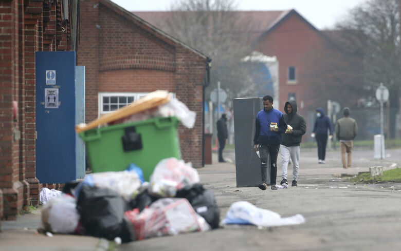 Migrants walk in  the grounds of Napier Barracks in Folkestone, Kent, England following a fire at the site, Sunday, Jan. 31, 2021. Police in southeast England have arrested five men following a disturbance at a former army barracks that has been housing around 400 asylum-seekers and where a fire broke out. Kent Police said a 31-year-old man was arrested on Friday on suspicion of assaulting a security guard in the wake of the fire at Napier Barracks on Friday afternoon. (Gareth Fuller/PA via AP)