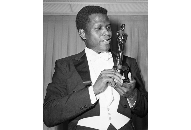"""FILE – Actor Sidney Poitier appears with his Oscar for best actor, for his role in """"Lillies of the Field,"""" at the 36th Annual Academy Awards in Santa Monica, Calif., on April 13, 1964. Arizona State University has named its new film school after Poitier. The university, which is expanding its existing film program into its own school, says it has invested millions of dollars in technology to create one of the largest, most accessible and most diverse film schools. The Sidney Poitier New American Film School will be unveiled at a ceremony on Monday, Jan. 25, 2021. (AP Photo, File)"""