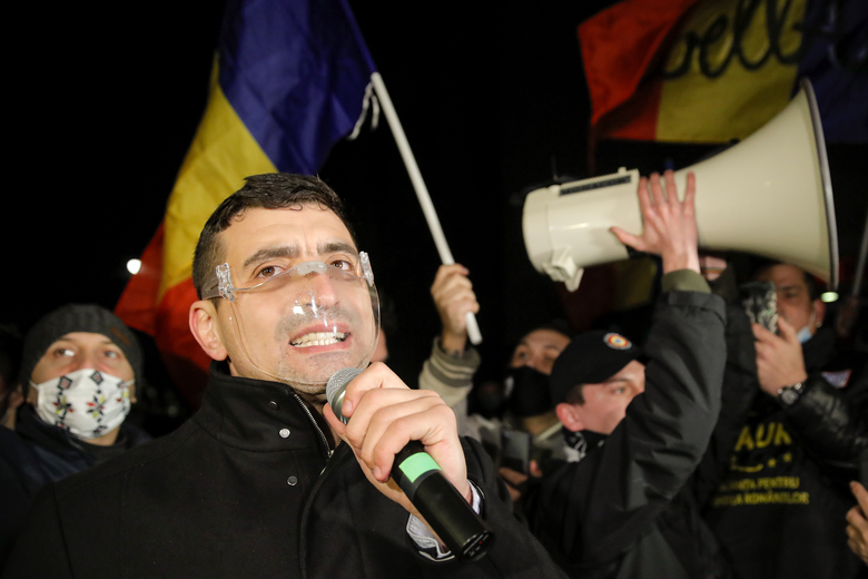George Simion, one of the leaders of the Alliance for the Unity of Romanians or AUR, speaks to protesters after a deadly fire at a hospital treating COVID-19 patients in Bucharest, Romania, Saturday, Jan. 30, 2021. Hundreds marched during a protest organized by the AUR alliance demanding the resignation of several top officials, after a fire early Friday at a key hospital in Bucharest that also treats COVID-19 patients killed five people. (AP Photo/Vadim Ghirda)