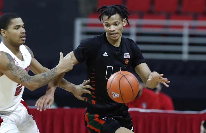 Miami's Isaiah Wong (2) takes the ball up court after it was stolen as North Carolina State's Shakeel Moore (2) trails during the second half of an NCAA college basketball game at PNC Arena in Raleigh, N.C., Saturday, Jan. 9, 2021. (Ethan Hyman/The News & Observer via AP)