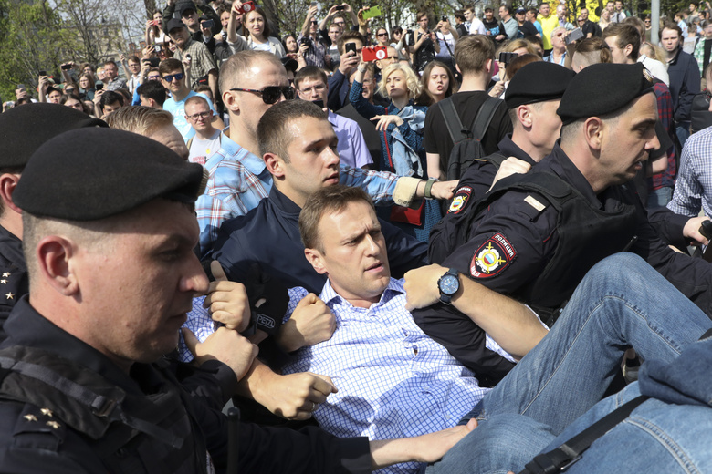FILE – In this May 5, 2018, file photo, Russian police carry opposition leader Alexei Navalny, center, from a demonstration against President Vladimir Putin in Pushkin Square in Moscow, Russia. Navalny is an anti-corruption campaigner and the Kremlin's fiercest critic. Frequently arrested, he has served multiple stints in jail for charges relating to leading protests. (AP Photo/File)