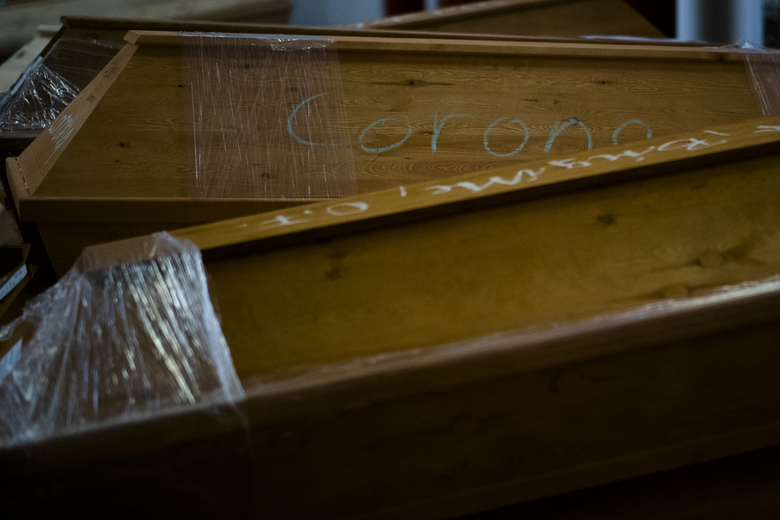 A casket labelled with the word 'Corona' is stacked with other coffins in the memorial hall of the crematorium in Meissen, Germany, Monday, Jan. 11, 2021. The crematorium would typically have 70 to 100 caskets on site at this time of year, now it has 300 bodies waiting to be cremated and more are brought to the crematorium every day. (AP Photo/Markus Schreiber)