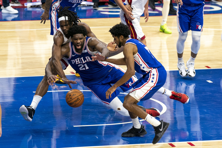 Philadelphia 76ers' Joel Embiid, center, battles with Miami Heat's Precious Achiuwa, left, for a loose ball as 76ers' Isaiah Joe, right, tries to help during overtime of an NBA basketball game Tuesday, Jan. 12, 2021, in Philadelphia. (AP Photo/Chris Szagola)