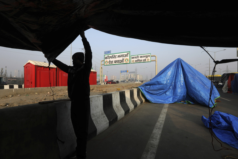 An Indian Farmer pitches his tent on the side of a highway, as they continue to block a highway leading to Delhi in protest against new farm laws, at Delhi-Uttar Pradesh border, India, Friday, Jan. 22, 2021. Talks between protesting farmers' leaders and the government ended abruptly in a stalemate on Friday with the agriculture minister saying he has nothing more to offer than suspending contentious agricultural laws for 18 months. The farmers' organizations in a statement on Thursday said they can't accept anything except the repeal of the three new laws. (AP Photo/Manish Swarup)