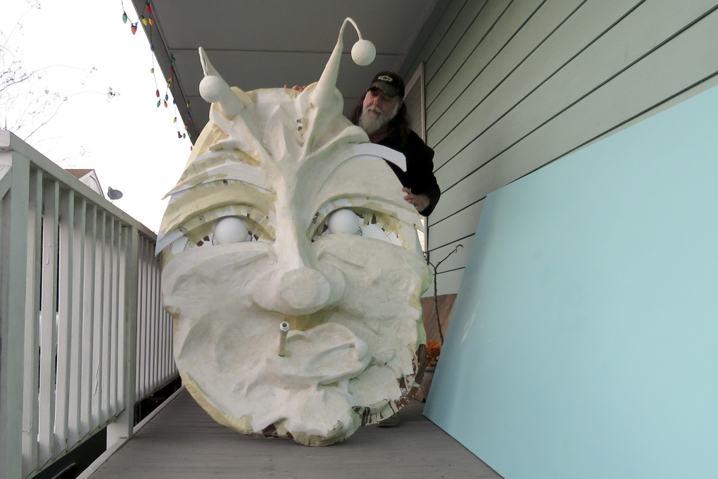 "Thom Karamus shows his paper mache head of the hookah-smoking caterpillar from ""Alice in Wonderland,"" on Wednesday, Jan. 14, 2021, in New Orleans. All around the city, thousands of houses are being decorated as floats because the coronavirus pandemic has canceled parades that usually take place on Mardi Gras. (AP Photo/Janet McConnaughey)"