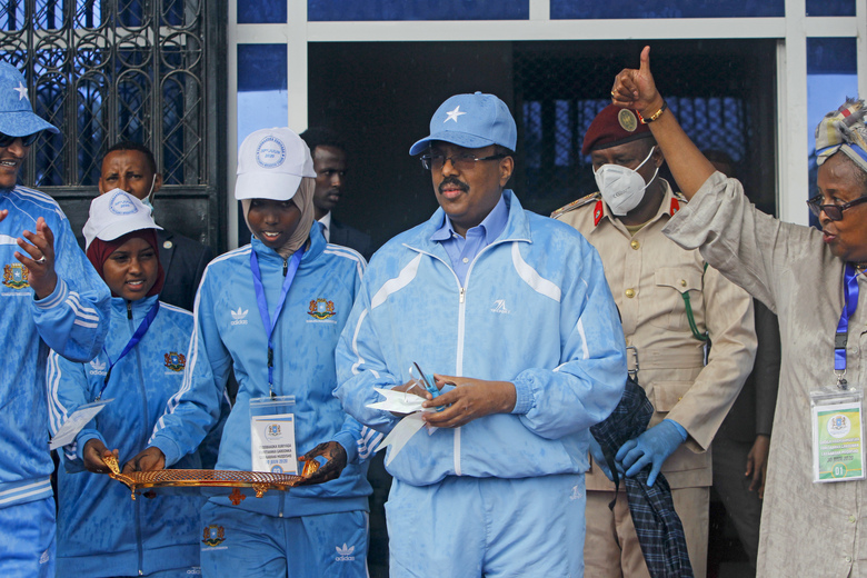 FILE – In this Tuesday, June 30, 2020, file photo, Somalia's President Mohamed Abdullahi Mohamed, center, prepares to cut the ribbon for the reopening of the stadium in Mogadishu, Somalia. As Somalia marks three decades since a dictator fell and chaos engulfed the country, the government is set to hold a troubled national election but two regional states are refusing to take part in the vote to elect Somalia's president and time is running out before the Feb. 8 date on which mandates expire. (AP Photo/Farah Abdi Warsameh, File)