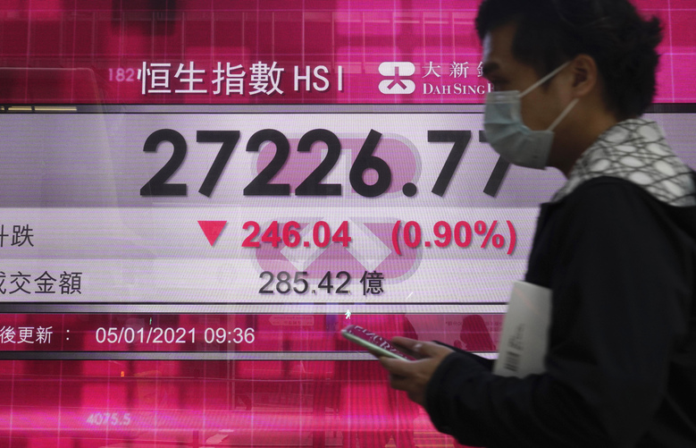 A man walks past a bank's electronic board showing the Hong Kong share index in Hong Kong Tuesday, Jan. 5, 2021. Asian shares were mostly lower Tuesday, echoing pullbacks on Wall Street, as worries grew about surging coronavirus cases in the region, with Japan preparing to declare a state of emergency. (AP Photo/Vincent Yu)