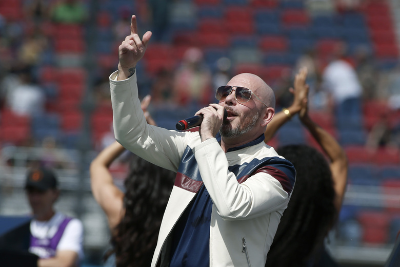 """FILE – Pitbull performs prior to a NASCAR Cup Series auto race at Phoenix Raceway in Avondale Ariz., in this Sunday, March 8, 2020, file photo. New NASCAR team Trackhouse Racing has brought entertainer Pitbull on as an ownership partner for an organization making its debut next month at the Daytona 500.  """"Mr. Worldwide"""" joins NBA Hall of Famer Michael Jordan as celebrity owners entering NASCAR this year. (AP Photo/Ralph Freso, File)"""