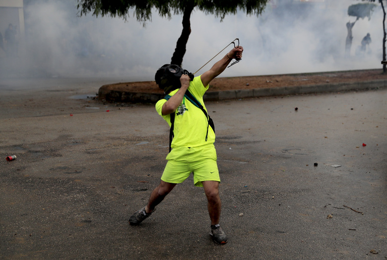 A protester fires a slingshot towards riot policemen, during a protest against deteriorating living conditions and strict coronavirus lockdown measures, in Tripoli, north Lebanon, Thursday, Jan. 28, 2021. Violent confrontations for three straight days between protesters and security forces in northern Lebanon left a 30-year-old man dead and more than 220 people injured, the state news agency said Thursday. (AP Photo/Hussein Malla)