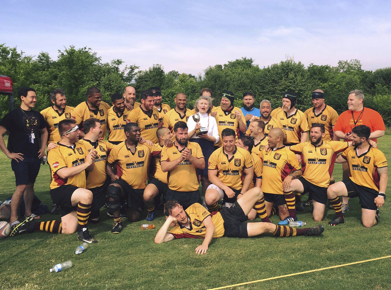In this photo provided by Megan Moran, Alice Hoagland, center standing, celebrates with the Philadelphia Gryphons rugby team May 27, 2016, in Nashville, Tennessee, after the team won the first Hoagland Cup at the world gay rugby tournament named for her son Mark Bingham, who died in the crash of United Flight 93 on Sept. 11, 2001. Hoagland, a Sept. 11 activist and a beloved figure in the world of gay rugby, died Dec. 22, 2020, her family said. (Courtesy of Megan Moran via AP)