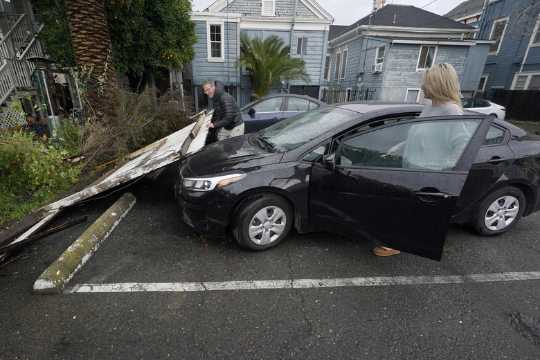 Bart Mehlhop, left, lifts a fence blown over on to Kelly Logue's car, by a storm that swept through Sacramento, Calif., overnight, Wednesday, Jan. 27, 2021. (AP Photo/Rich Pedroncelli)