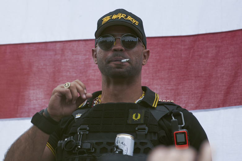 "FILE – In this Sept. 26, 2020, file photo, Proud Boys leader Henry ""Enrique"" Tarrio wears a hat that says The War Boys during a rally in Portland, Ore. Police in the nation's capital on Jan. 4, 2021, arrested the leader of the Proud Boys, who is accused of burning a Black Lives Matter banner that was torn down from a historic Black church in downtown Washington in December 2020. (AP Photo/Allison Dinner, File)"