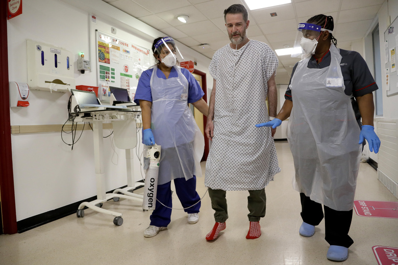 Felicia Kwaku, Associate Director of Nursing, right, and Anna Castellano, Matron, left, help COVID-19 patient Justin Fleming walk again after recovering, on the Cotton ward at King's College Hospital in London, Wednesday, Jan. 27, 2021. Fleming is one of more than 37,000 coronavirus patients being treated now in Britain's hospitals, almost double the number of the spring surge. King's College Hospital, which sits in a diverse, densely populated area of south London, had almost 800 COVID-19 patients earlier this winter. (AP Photo/Kirsty Wigglesworth, pool)
