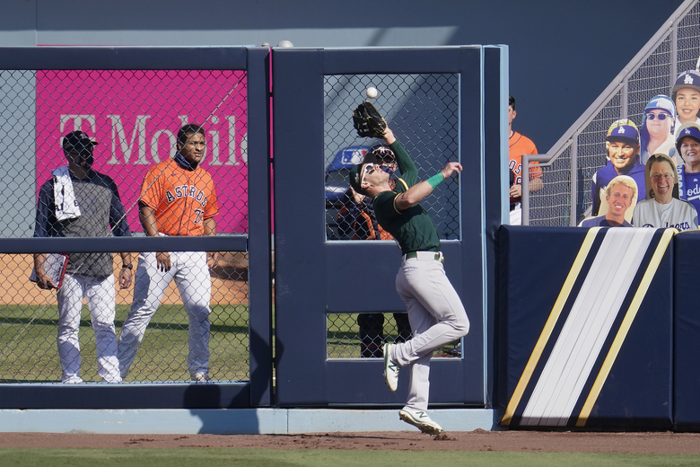 Oakland Athletics right fielder Mark Canha catches Houston Astros' Aledmys Diaz's fly out during the sixth inning of Game 3 of a baseball American League Division Series in Los Angeles, Wednesday, Oct. 7, 2020. (AP Photo/Marcio Jose Sanchez)