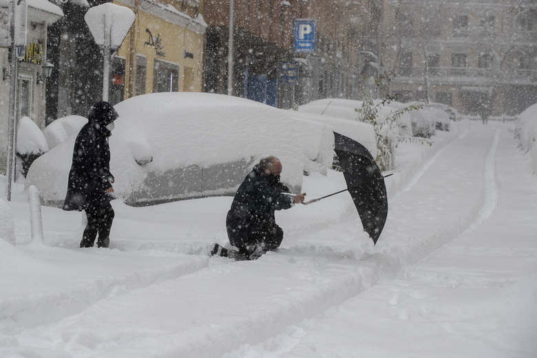 A man slips and falls crossing the street during a heavy snowfall in central Madrid, Spain, Saturday, Jan. 9, 2021, prompting a red weather alert and military assistance to rescue people trapped in cars. An unusual and persistent blizzard has blanketed large parts of Spain with snow, freezing traffic and leaving thousands trapped in cars or in train stations and airports that had suspended all services as the snow kept falling on Saturday.(AP Photo/Paul White)