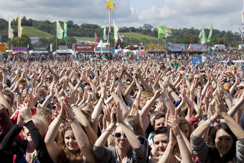 FILE – In this Friday, June 24, 2011 file photo, the crowd at Glastonbury Music Festival clap their hands above their heads as they watch Chipmunk on stage, Glastonbury, England. Britain's Glastonbury music festival has fallen victim to the coronavirus pandemic for the second year in a row, organizers Michael Eavis and Emily Eavis said Thursday Jan. 21, 2021. (AP Photo/Joel Ryan, File)