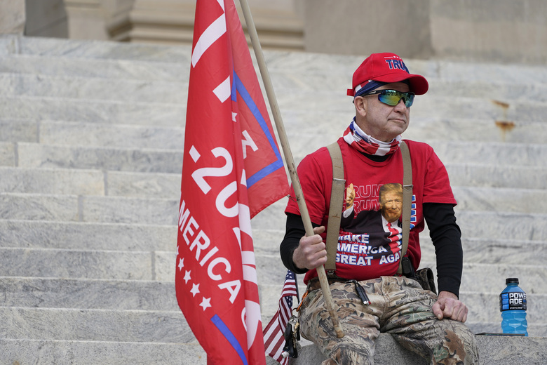 An unidentified participant of a pro-Trump protest sits on the steps of the Mississippi Capitol after the small rally concluded, Wednesday, Jan. 6, 2021 in Jackson, Miss. The gathering served a dual purpose of protesting the constitutional process to affirm the president-elect's victory in the November election and to call for a revote over the state flag issue. (AP Photo/Rogelio V. Solis)
