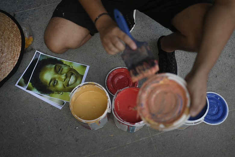Photographs of Venezuelan athlete Yulimar Rojas lay next to cans of paint as street artist Wolfgang Salazar prepares to work  on an art mural featuring Rojas, in the Boleita neighborhood of Caracas, Venezuela, Monday, Dec. 28, 2020. Salazar has gained increasing fame for his spray-painted murals of Venzuelans — heroes and everyday folk alike — at a time when the pandemic and economic hardship weigh upon his fellow citizens. (AP Photo/Matias Delacroix)