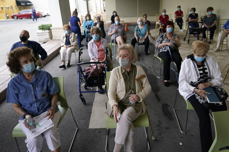 FILE – In this Jan. 12, 2021, file photo, residents wait to be cleared after receiving the Pfizer-BioNTech COVID-19 vaccine at the The Palace assisted living facility in Coral Gables, Fla. Florida Gov. Ron DeSantis is walking back his claims that his state has now vaccinated 1 million seniors. State officials acknowledged that it could take a few more days to reach the milestone. (AP Photo/Lynne Sladky, File)
