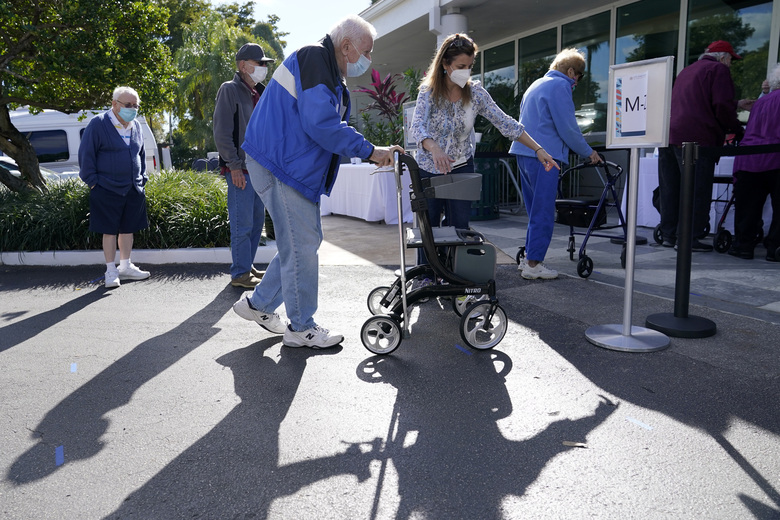 FILE – In this Jan. 19, 2021, file photo, Robert Owens, 90, stands in line with other residents to receive the Pfizer-BioNTech COVID-19 vaccine at John Knox Village in Pompano Beach, Fla. Florida Gov. Ron DeSantis is walking back his claims Friday, Jan. 22, that his state has now vaccinated 1 million seniors. State officials acknowledged that it could take a few more days to reach the milestone. (AP Photo/Lynne Sladky, File)