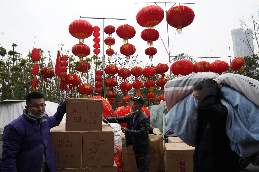 Workers move stock near lanterns on sale for the upcoming Chinese Lunar New Year in Wuhan in central China's Hubei province on Friday, Jan. 22, 2021. Life appears to be back to normal on the eve of the anniversary of the 76-day lockdown in the central Chinese city where the coronavirus was first detected. (AP Photo/Ng Han Guan)