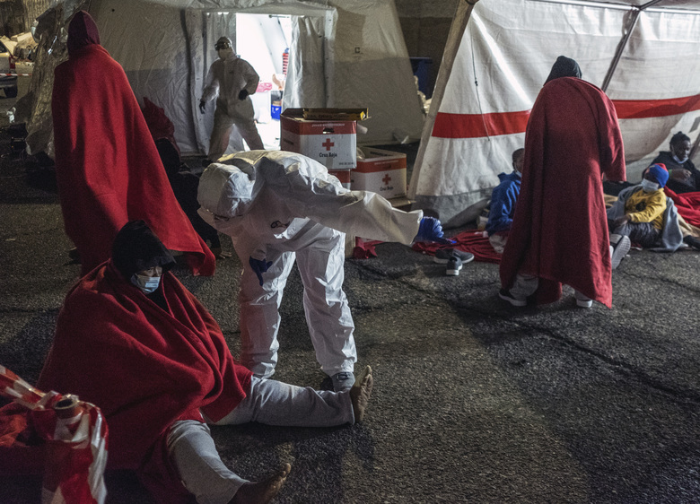 Rescued migrants sit inside a tent in the port of Arguineguin, Gran Canaria island, Spain, Saturday Jan. 16, 2021. A Spanish rescue ship rescued a boat 160 kilometres south of Gran Canaria with men, women and children on board in very poor condition. (AP Photo/Javier Bauluz)