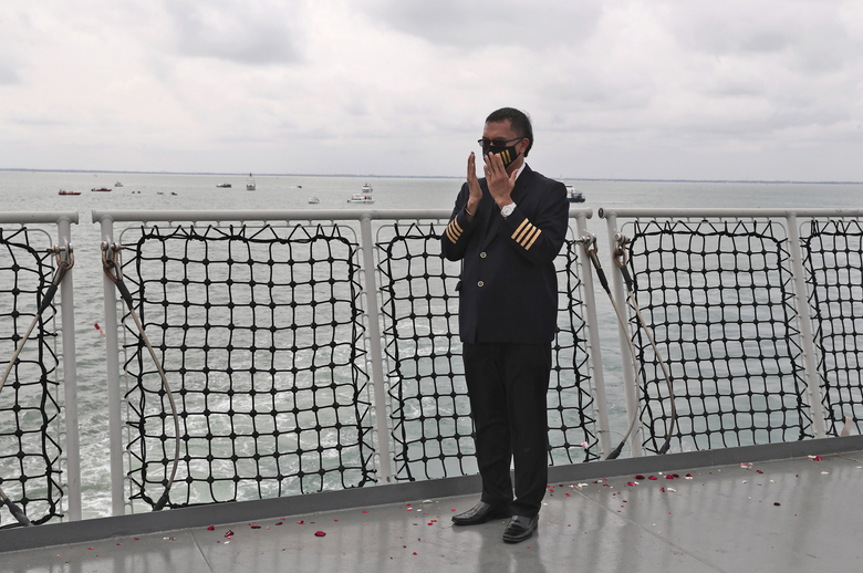 An Indonesian pilot prays during a memorial ceremony for the victims of Sriwijaya Air flight SJ-182 on the deck of Indonesian Navy Ship KRI Semarang that sails in the Java Sea where the plane crashed on Jan. 9 killing all of its passengers, near Jakarta in Indonesia, Friday, Jan. 22, 2021. (AP Photo/Tatan Syuflana)