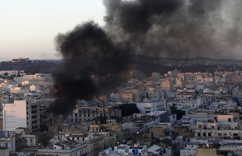 FILE – In this file photo dated Friday, Jan. 14, 2011, a column of smoke rises from buildings during clashes between protesters and police in Tunis. Tunisia's president declared a state of emergency and announced that he would fire his government as violent protests escalated Friday, with gunfire echoing in the North African country's usually calm capital and police lobbing tear gas at protesters. On Thursday Jan. 14, 2021, Tunisia commemorates 10 years since the flight into exile of its iron-fisted leader, Zine El Abidine Ben Ali, pushed from power in a popular revolt that foreshadowed the so-called Arab Spring.(AP Photo/Christophe Ena)
