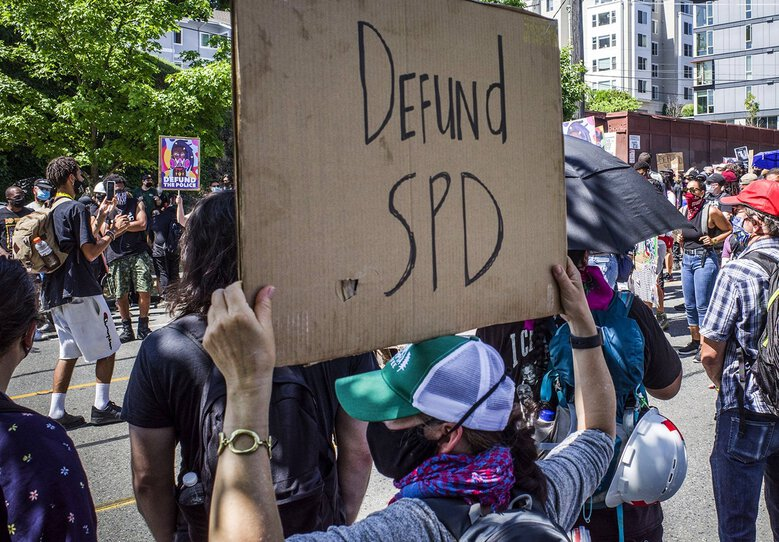 Marchers organized by Decriminalize Seattle and King County Equity Now gather across from the new youth jail to head to City Hall to call for police defunding on Aug. 5, 2020. (Steve Ringman / The Seattle Times)
