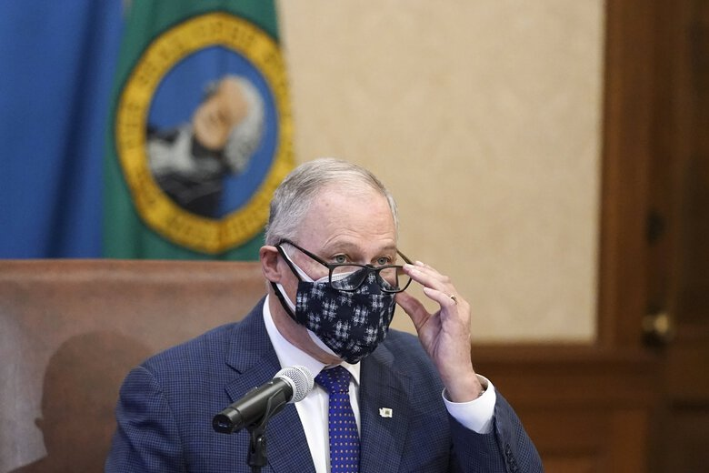 Washington Gov. Jay Inslee wears a double mask as he speaks before signing the first bill to be signed into law during the 2021 legislative session, Monday, Feb. 8, 2021, at the Capitol in Olympia. The measure increases the minimum weekly benefit for unemployed workers during the ongoing coronavirus pandemic and prevents a dramatic increase in unemployment taxes paid by businesses. (Ted S. Warren / The Associated Press)
