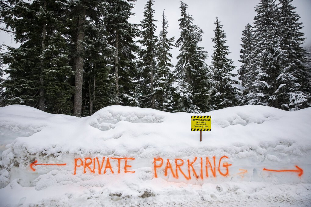The Sahalie Ski Club spray-painting their private parking areas to keep them open for members but closed to visitors as people looking to play in the snow spill out from the parking lots at Alpental at Snoqualmie Pass. (Bettina Hansen / The Seattle Times)
