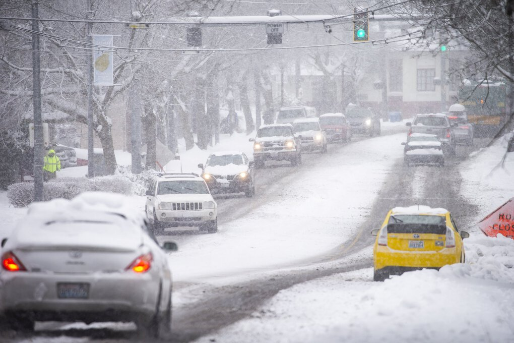 Snow continues to fall, picking up in the mid-afternoon along Rainier Avenue South in Columbia City Saturday February 13, 2021. (Bettina Hansen / The Seattle Times)